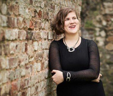Ema nikolovska sorride poggiata su un muro