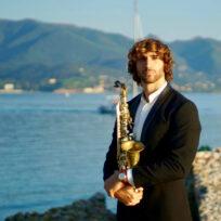 Jacopo taddei con il sax in riva al mare